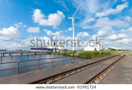 chemical tankers moored in amsterdam harbor next to a large windmill and railroad