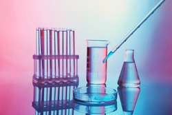 Chemical test-tubes with medicine dropper on color background