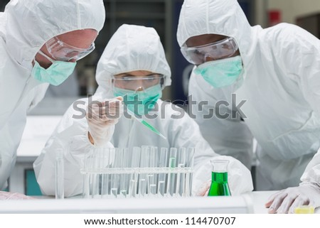 Chemist adding green liquid to test tubes with two other chemists watching in the lab