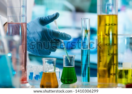Chemist mixing fluids with a pipette in the research laboratory / hand of researcher with pipette measuring sample in beaker of liquids in the chemical lab