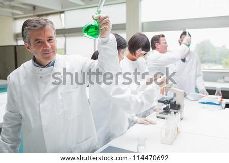 Chemist raising beaker of green liquid in busy lab