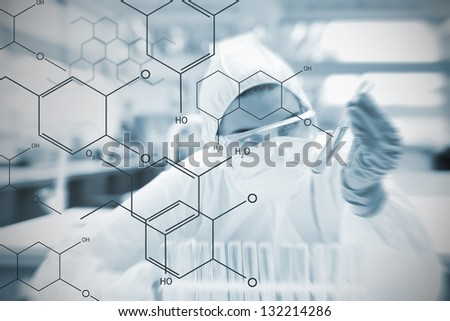 Chemist working cautiously with liquid and futuristic interface showing formula in soft focus effect