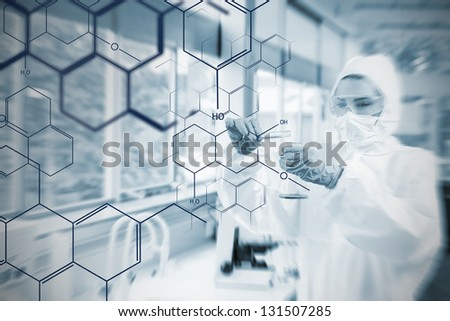 Chemist working cautiously with liquid helped by futuristic interface in soft focus effect