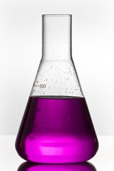 chemistry glass with toxic violett liquid on white ground