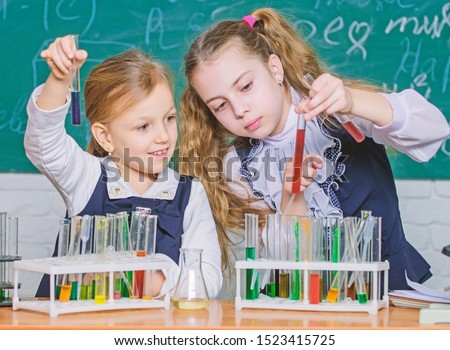 Chemistry is about reaction. Smart school children performing chemistry test in lab. Small schoolgirls learning chemistry during school time. Little pupils holding test tubes in chemistry laboratory.