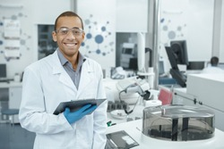 Chemistry is his passion. Handsome young African male scientist wearing protective glasses smiling happily holding his clipboard working at the lab professionalism occupation job people copyspace