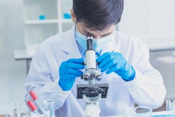 Chemistry lab male students scientist look into Microscope researching science laboratory. Asian student chemistry scientist look microscope laboratory chemistry labs covid-19 coronavirus biochemistry