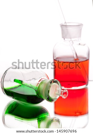 Chemistry laboratory glassware with colour liquids in them on white background