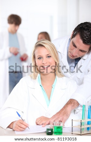 Chemistry student being helped by her teacher