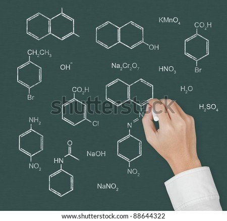 chemistry teacher hand writing scientific  formula of chemical on chalkboard