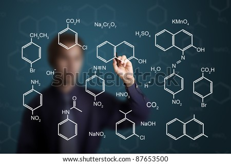 chemistry teacher writing scientific  formula of chemical on white board