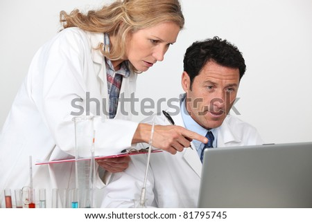 Chemists looking at laptop - stock photo
