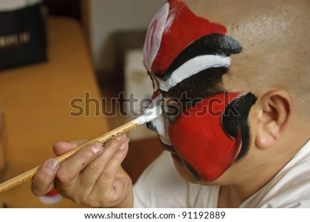 CHENGDU, CHINA - JULY 26: An unidentified Chinese opera actor is painting his face backstage at JinJiang theater on July 26, 2007 in Chengdu, China.