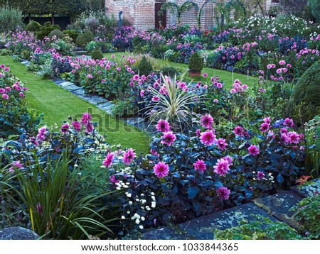 CHENIES MANOR TUDOR GARDEN AND PAVILION GALLERY, CHENIES, BUCKINGHAMSHIREM, ENGLAND, AUGUST 2014. The impressive sunken garden with a colourful display of Dahlias in late summer and the Tudor Pavilion #1033844365