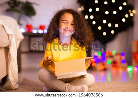Cherished present. Cheerful afro girl enjoying her glowing Christmas present at home