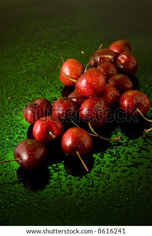 cherries and water drops still life over green background