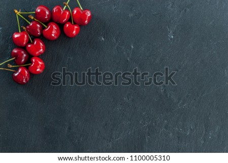 cherries arranges as a frame on black with copy space #1100005310