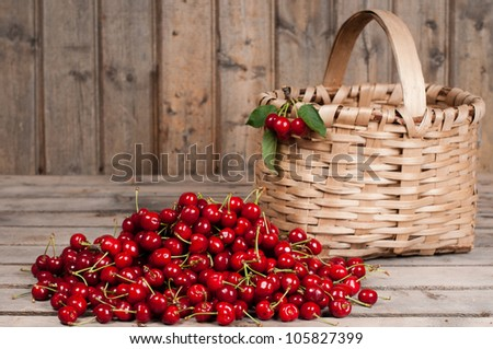 Cherries in a basket on an old wood background - stock photo
