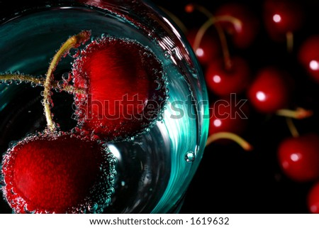 cherries in a drink with bubbles