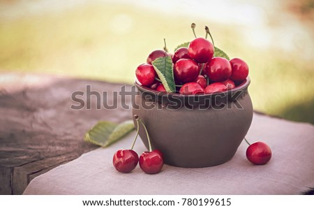 Cherries in ceramic bowl. Red cherry and leaf in bowl and napkin on wooden background with sunlight. Fresh cherries bowl as healthy and fruitarians concept. Sweet cherries in bowl on old stump.