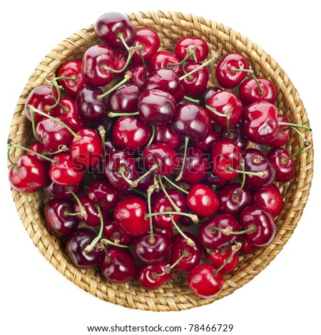 cherries on wicker plate basket surface top view close up isolated on white  background