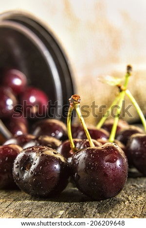 Cherries on wooden table with water drops.
