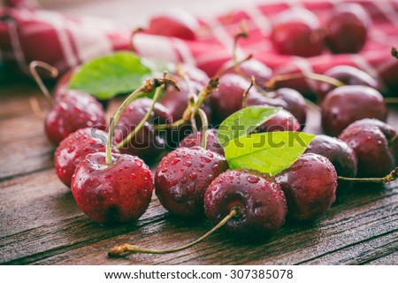 Cherries on wooden table with water drops