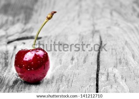 Cherries on wooden table with water drops macro background