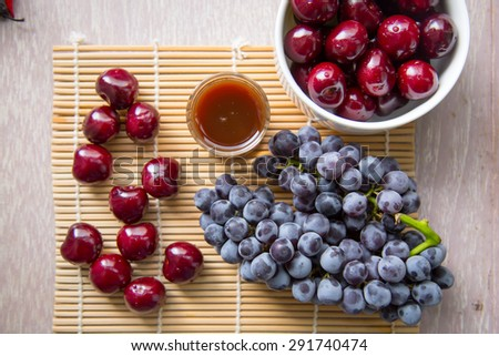 Cherry and grape fruits and juice grass on wooden table