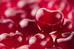 Cherry background with cherry in form of heart. Ripe fresh rich cherries. Macro. Texture.   Fruit background. Valentine's Day.