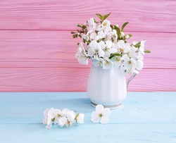 cherry blossoms in a vase on a wooden background