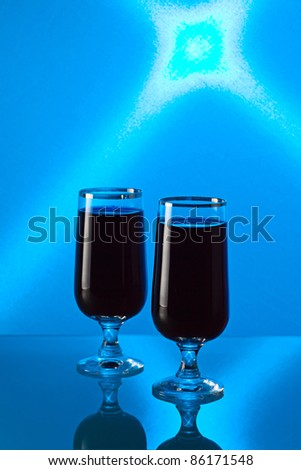 Cherry brandy on a glass table, a background is shined by the blue filter.