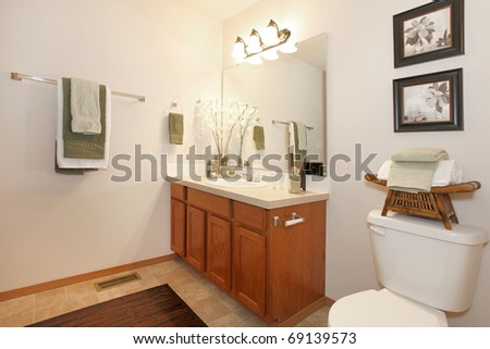 Cherry cabinet and yellow curtains in bathroom with art.