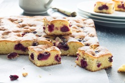 Cherry cake and slices of cherry cake on a baking paper