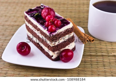 Cherry cake with cinnamon  and coffee cup on the table