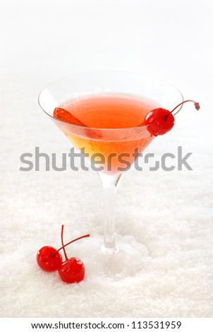 Cherry cocktail in a martini glass decorated with maraschino cherries, on snow.