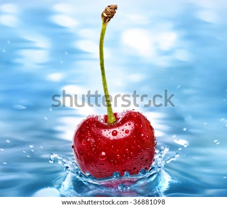 Cherry falls into the cold aqua water surface close up macro
