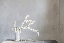 cherry flowers in white jug on old wooden table