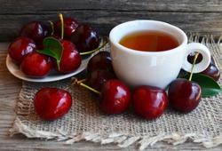 Cherry fruit tea with freshly picked cherries in a white cup on a burlap cloth.Selective focus