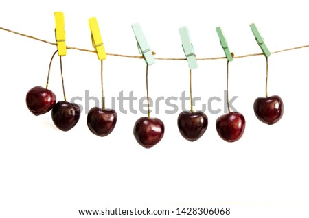 Cherry hangs on a clothespin on a rope. Seven cherries hanging on clothespins in various colors - yellow, blue on a white background. Insulator. Close-up. Horizontal