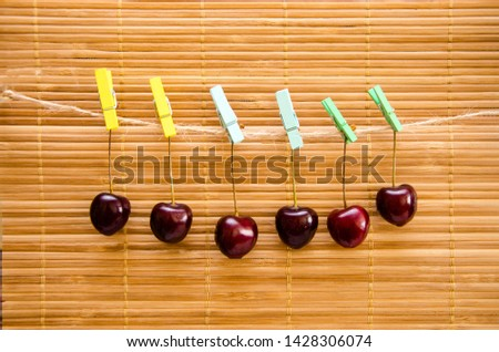 Cherry hangs on a clothespin on a rope. Six cherries hanging on clothespins in various colors - yellow, blue, green on a bamboo background. Close-up. Horizontal