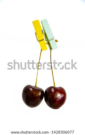 Cherry hangs on a clothespin on a rope. Two cherries hanging on clothespins in various colors - yellow, blue, green on a bamboo background. Close-up. Horizontal