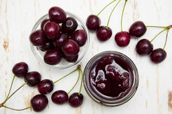 Cherry jam with fresh cherries on a wooden background