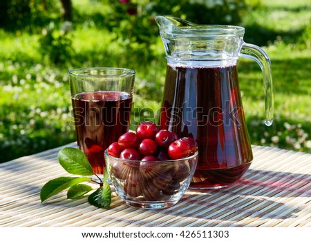 cherry juice in a glass and carafe with cherries on natural background