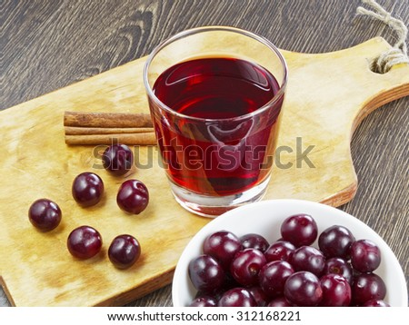 cherry juice in a glass on wooden table