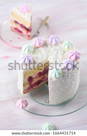 Cherry Layer Cake decorated with fine coconut flakes and colored meringue cookies, on white wooden background. Foto d'archivio ©