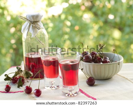 Cherry liquor in glass on natural background. Selective focus
