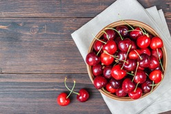 Cherry on plate bowl on wooden background. Ripe ripe cherries. Sweet red cherries. Top view Rustic style