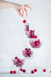 Cherry on top of a balancing stack of bowls and cups filled with berries. Final touch concept on a white background with copy space