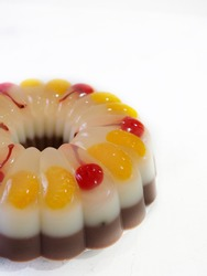 cherry - orange jelly pudding with three layer (orange and cherry, white milk and chocolate). With grainy textured and gritty lines. white isolated and background